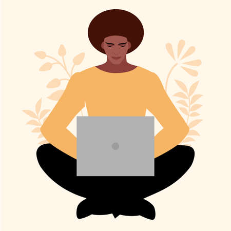 African young man sitting comfortably with a laptop, surrounded by plants