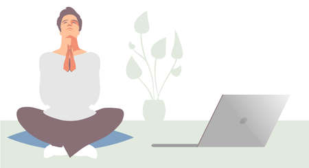 Young businessman sitting in the lotus position, meditating, next to his laptop, in a relaxed atmosphere with plant in the background.