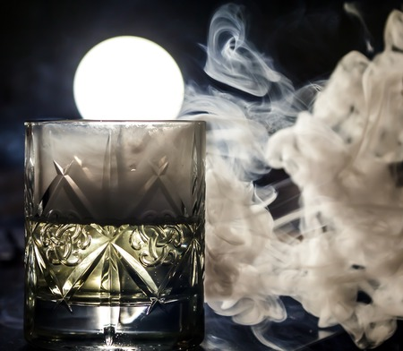 a glass of whiskey in the smoke