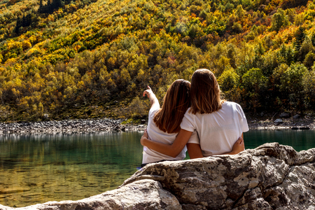 two girls on the Lake admiring the forest