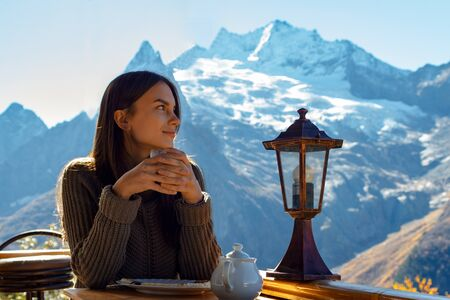 Girl drinks tea against the backdrop of mountains