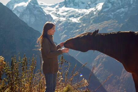 Girl with a horse in the background of mountains Stok Fotoğraf