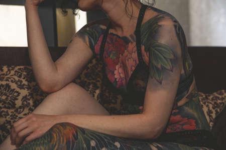 tatoo girl on the sofa in home
