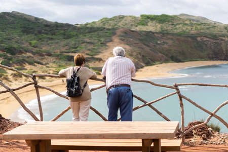 Es Mercadal, Baleari Islands / Spain; 10 02 2015: Couple with their backs to a wooden bench leaning on a branching beam, watching the beautiful and natural red beach of Cavalleria under their feet 新聞圖片