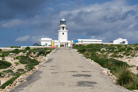 Es Mercadal, Baleari Islands / Spain; 10 02 2015: Paved road to the Cavallería lighthouse, in the background of the image under an intense blue sky with large gray clouds