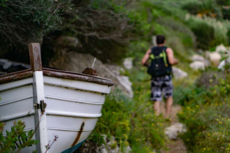 Prow of a small boat abandoned in nature next to a cove, next to a path traveled by a tourist with his back turned Stock Photo