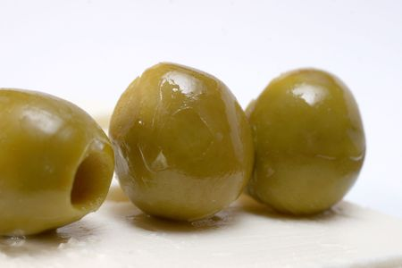 closeup image of couple olives on cheese plate