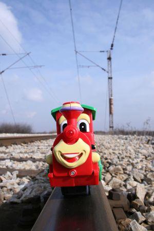 imafe of one smile toy locomotive on realy railway Stock Photo