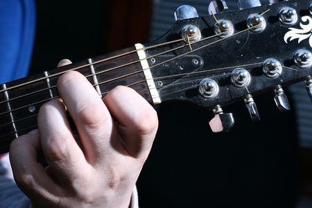 closeup image of one hand that plays guitar
