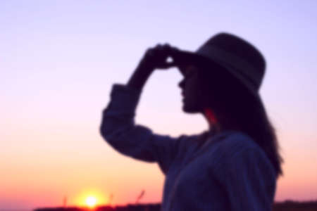 Blurry silhouette of teenage girl wearing a sun hat and looking to the left, close up portait, space for text. Female portrait, sunset background, cropped shot. People, travel concept.