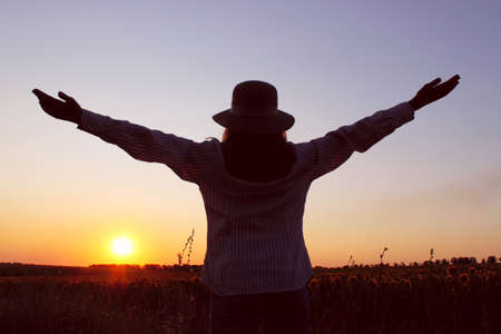 Blurred silhouette of a woman looking to the sunset and holding hands up. Cropped shot of a girl outdoor. People, travel concept. Teenage girl looking to the beautiful landscape. Banque d'images