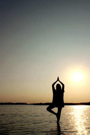 Silhouette of Teenage Girl In A Balancing Yoga Position. Young Girl In Tree Pose Position, Outdoors.