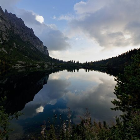 Mirror reflection of mountains and sky with clouds in Poprad lake, High Tatras, Slovakia, forest on the horizon Reklamní fotografie