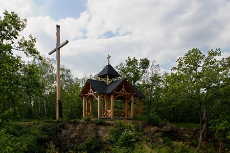 Modern wooden chapel with high wooden cross in forest above rocky wall at Maly Kosir hill, Czech Republic