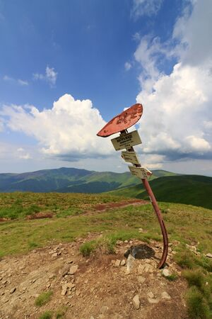 Damaged and bented rusty tourist signpost in carpathian mountains, Ukraine. Green mountain ridge and blue sky with white clouds.