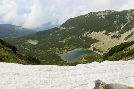 View of Bansko lake in the valley in Rila mountains, Bulgaria. Shot was made over edge of snowdrift.