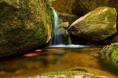 Small waterfall on a mountain stream, Cold stream between mossy rocks, milk effect and vivid colors,  Jizera mountains, Czech Republic
