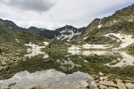 Mount Musala covered with many snowfields, reflected on water surface of small mountain lake. Panoramic view, Rila mountains, Bulgaria. Mount Musala is the highest peak in Bulgaria and on Balkan peninsula. Imagens