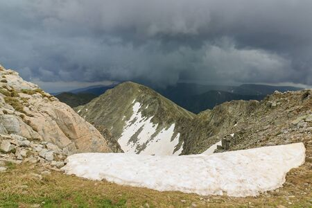 Panoramic view in Rila mountains , Bulgaria. Dramatic clouds before storm. Dnowdrift and snowfields on rocky mountain ridge. Imagens