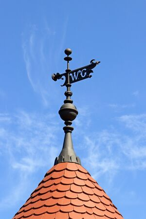 Black steel WC sign in weather vane (wind vane, weathercock) style. Red tiled roof and blue sky.