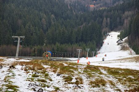 Snow cannons are deployed on the slope and ready for their work. A narrow strip of snow with ski lift between forests.