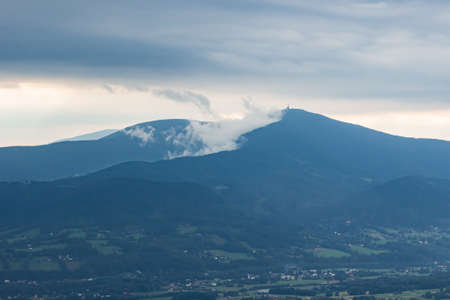 Silhouette of mountain ridge against cloudy sky. Mist rising from woods. Lysa hora peak in Beskydy mountains, Czech Republic. Summer day after rain. Banco de Imagens