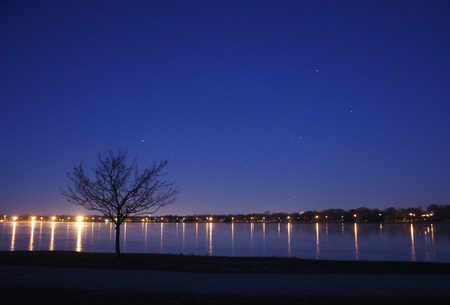 orion: The night sky fades to morning light and Orion the Hunter begins to sink to the horizon, below the city lights, and the frozen lake.