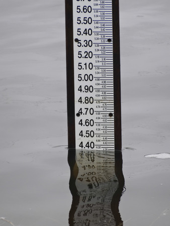 A staff gauge marks the progress of rising flood waters.