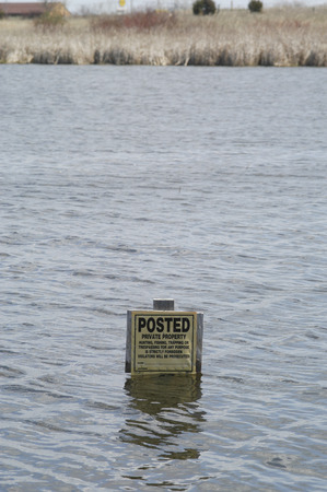 trespassing: A no trespassing sign is nearly drowned in the rising floodwaters of a lake.