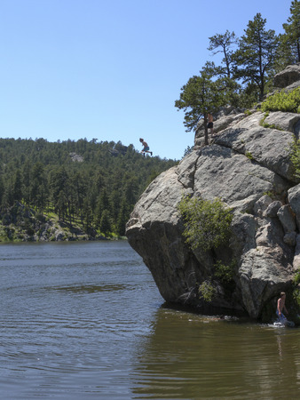 A swimmer leaps from a cliff into Horsethief Lake in the Black Hills of South Dakota.  There is no way I'd jump from that cliff to swim in the ice cold water. photo