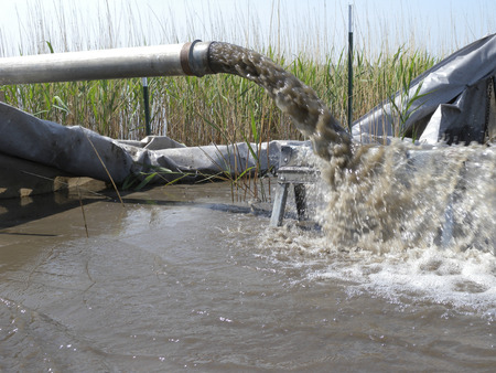 dredging: Sand dredge spoils pour out of a pipe and form a new sand bar as part of conservation project. Stock Photo