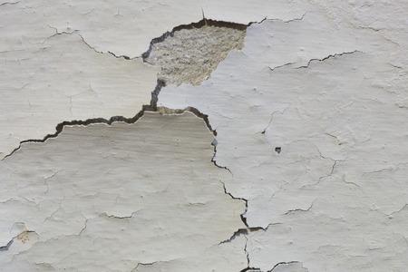 De oude verf op een betonnen muur kelder is kraken en peeling weg van het beton.