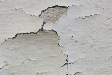 The old paint on a basement concrete wall is cracking, and peeling away from the concrete.