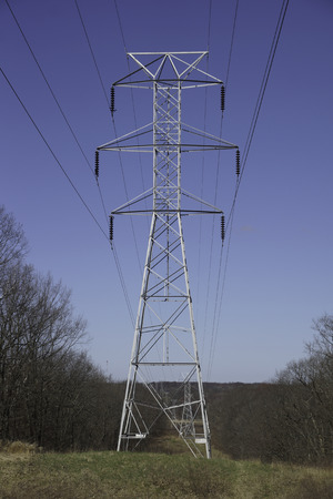 far off: The metal skeletal structure of electrical high voltage power pole and power lines.  These eyesores in the landscape bring much needed electrical power from far off power plants. Stock Photo