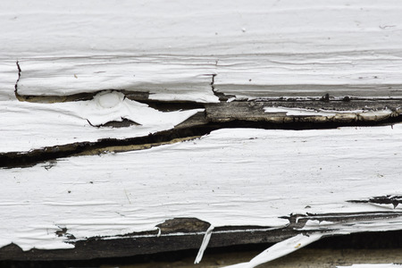 The peeling paint on the rotting wood siding of a garage. Stock Photo