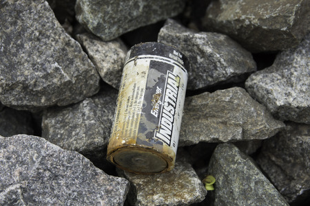 A corroded industrial D battery on a pile of stone.