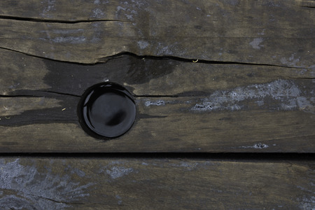 creosote: Water filled hole in a wooden railroad tie.