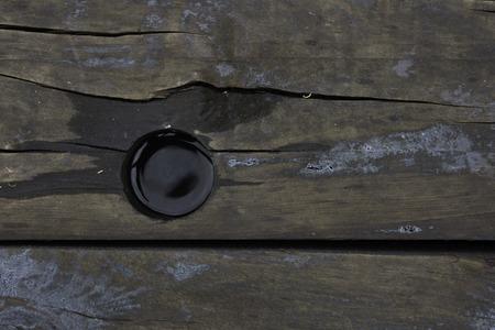 railroad tie: Water filled hole in a wooden railroad tie.