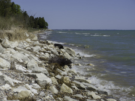 The Lake Michigan shoreline erodes away as waves crash in on a beautiful day.