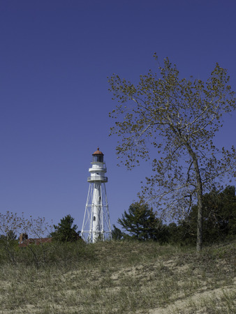 lake michigan lighthouse: Rawley Point Lighthouse on the Wisconsin side of Lake Michigan peaks over a sand dune.