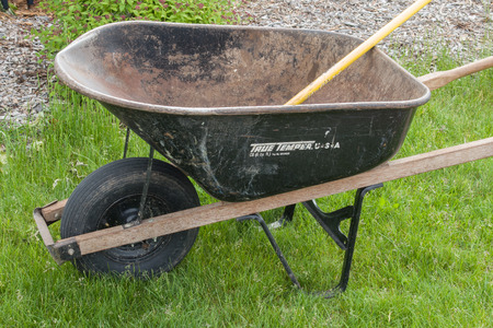 dump yard: A black wheelbarrow sits on the lawn ready to get to work in the garden.
