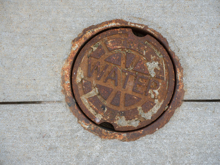 Rusty Iron cover provides access to a water main.