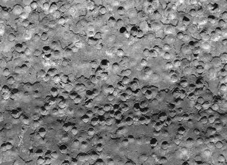 The pellets from a shotgun blast have made craters in an aluminum sign making it look like the surfacce of the moon.