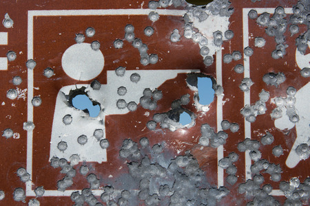 full of holes: A recreation sign that shows hunting is allowed is shot full of bullet holes. Stock Photo