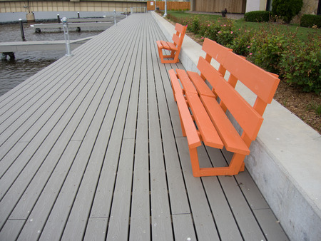 provide: Orange park benches provide a place to rest on a river walk.