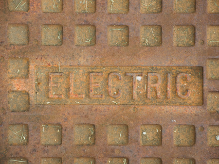 A rusty manhole cover with the word Electric on it, describing what utilities the cover gives access to.