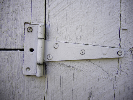 The painted hinge screwed into the boards of a barn door. Фото со стока