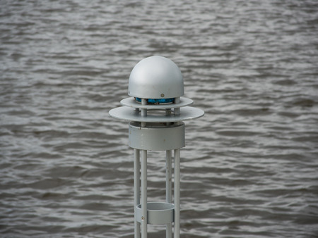 light fixture: There is a blue lightbulb in this metal outdoor light fixture, by the water.