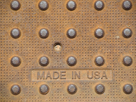 A heavy, rusty steel plate proudly stamped made in USA at the foundry.   It also has interesting dot patterns that provide traction for walking on. Imagens