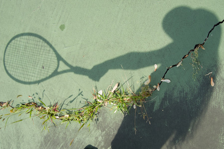 Shadow of girl with a tennis racket and neglected and broken tennis court.  Sports programs around the country face budget cuts. Imagens